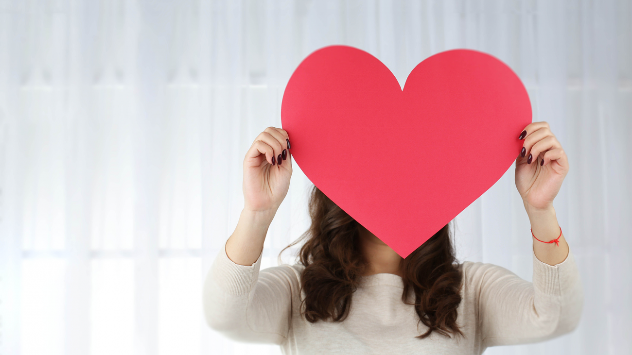 Photo of woman holding up paper cutout of heart over face