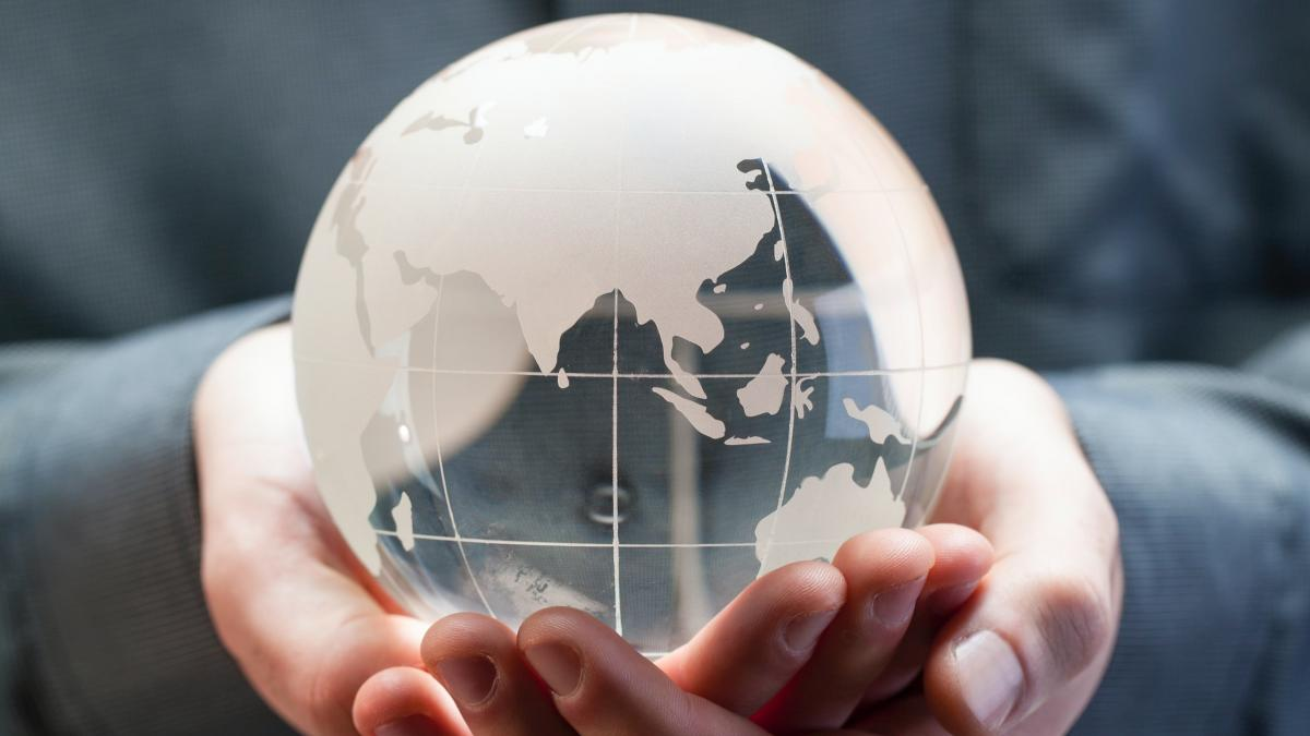 Photo of a person holding a glass globe of the Earth in their hands.